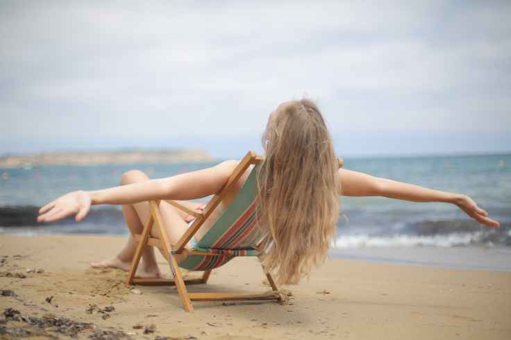 woman in blue and brown bikini sitting on brown wooden folding chair on beach